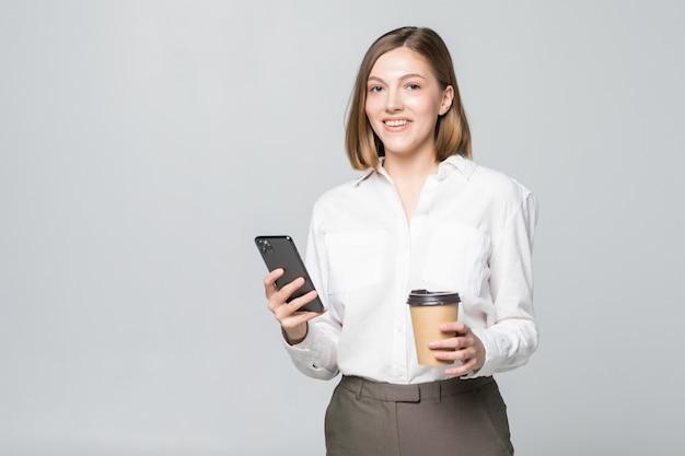 Ritratto di una donna d'affari giovane soddisfatta utilizzando il telefono cellulare mentre si tiene la tazza di caffè per andare isolato sopra il muro bianco