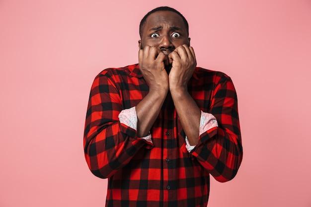Ritratto di un uomo africano spaventato che indossa una camicia a quadri in piedi isolato su un muro rosa, facendo una smorfia