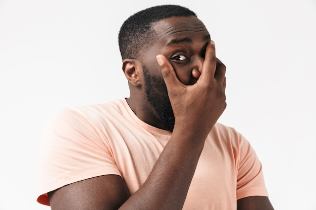 Ritratto di un uomo africano spaventato che indossa una maglietta in piedi isolato su un muro bianco, copre la bocca