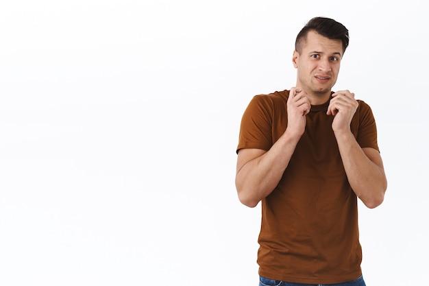 Ritratto di un bel giovane uomo alla moda spaventato e insicuro, tieni le mani premute sul petto per evitare qualcosa di disgustoso o spaventoso