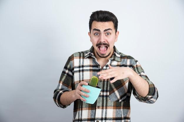 Ritratto di uomo spaventato mantenendo piccolo cactus in vaso blu sopra il muro bianco.