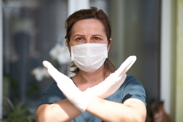 Ritratto di donne spaventate che mostrano il segno no, incrociando le braccia, mantenendo la distanza, indossando guanti e maschera antibatterica, guardando direttamente la telecamera, trovandosi in quarantena.