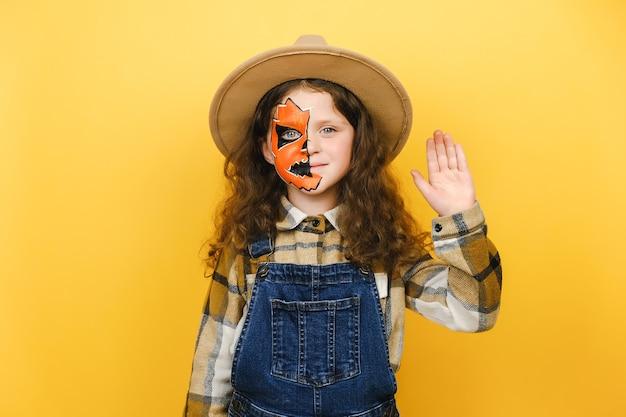 Ritratto di spaventoso brillante vivo divertente ragazza bambino con trucco di halloween, vestito con cappello e camicia, agitando la mano in gesto di saluto in piedi isolato su sfondo giallo studio. concetto di festa di festa