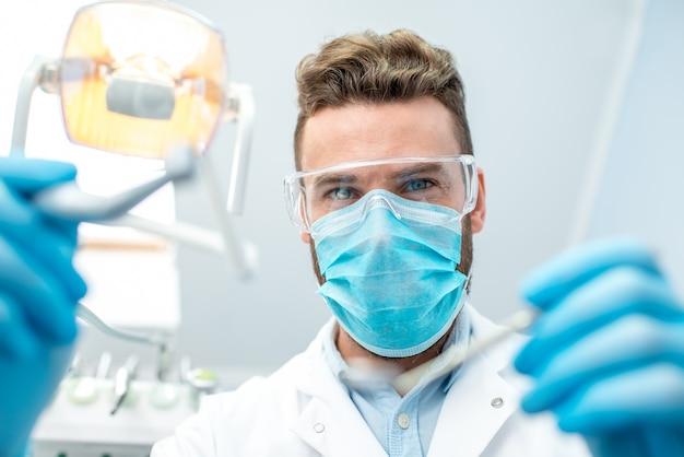 Ritratto di un dentista spaventoso in maschera e occhiali protettivi con strumenti dentali durante l'intervento chirurgico che guarda la telecamera