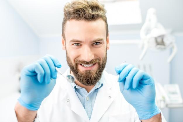 Ritratto di un dentista spaventoso con strumenti dentali che guarda la bocca in telecamera