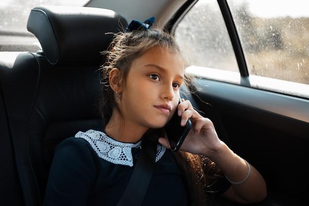 Ritratto di ragazza della scuola che parla allo smartphone in macchina.