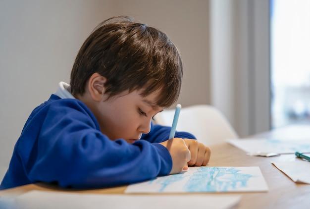 Ritratto di ragazzo di scuola seduto da solo a fare i compiti, bambino ragazzo che tiene penna a colori disegno e scrittura su carta bianca sul tavolo, scuola elementare e concetto di homeschooling