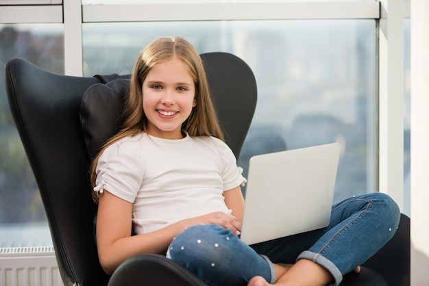 Il ritratto della ragazza sorridente della scuola si siede con il computer portatile Foto Premium