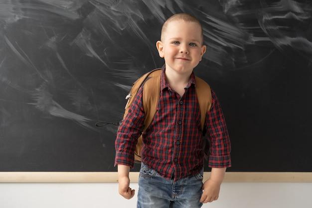 Ritratto di uno scolaro che è in piedi davanti alla lavagna e sorridente. la lavagna è pulita con tracce di gesso. il bambino è vestito con una camicia scura e jeans. .