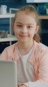Ritratto di studentessa utilizzando laptop per i compiti e sorridente