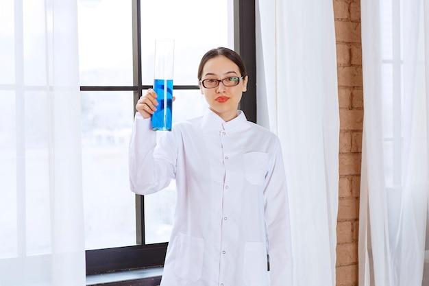 Ritratto della donna dello scienziato in camice da laboratorio che tiene liquido blu chimico.