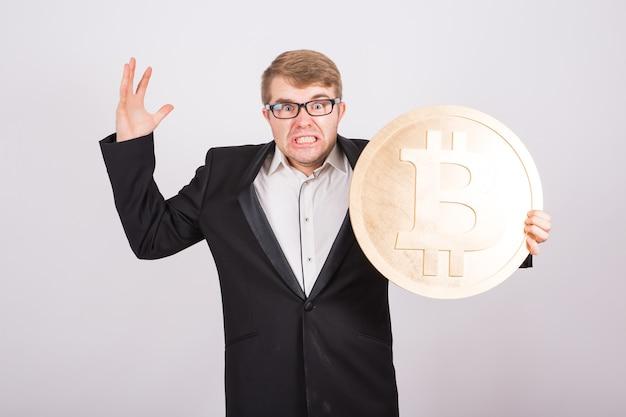 Ritratto di un uomo d'affari urlante tiene grande bitcoin dorato tra le braccia. uomo in preda al panico per il crash della criptovaluta.