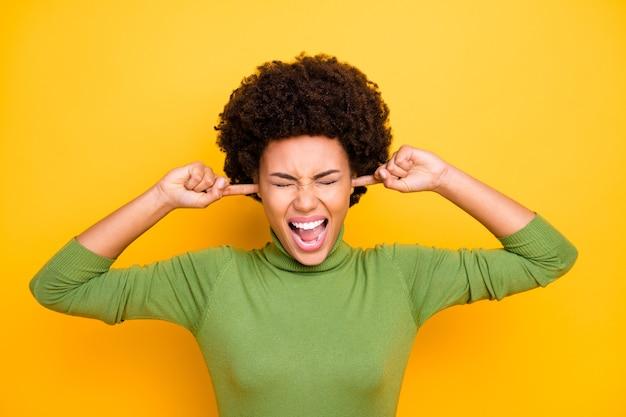 Ritratto di ragazza che grida grida fa smorfie chiudendo le orecchie per non sentire nulla di irritato infastidito dalle persone circostanti.