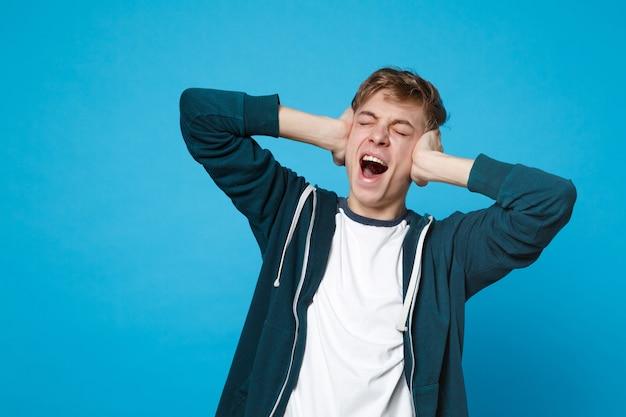 Ritratto di un giovane urlante in abiti casual che tiene gli occhi chiusi, coprendo le orecchie con le mani isolate sul blu. Foto Premium