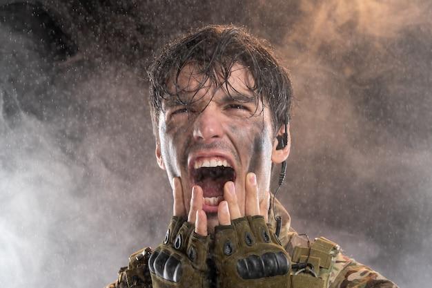 Ritratto di giovane soldato urlante in uniforme sul muro scuro