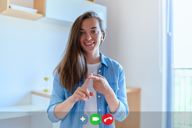 Visualizzazione dello schermo verticale di una giovane ragazza sorridente felice e carina durante i corsi di lingua dei segni online a casa utilizzando la conferenza webcam sul computer