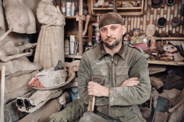 Ritratto dell'uomo della scultura nel suo studio domestico
