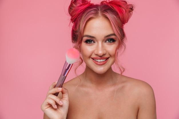 Ritratto di donna seducente senza camicia con acconciatura colorata che applica cosmetici con pennello per il trucco