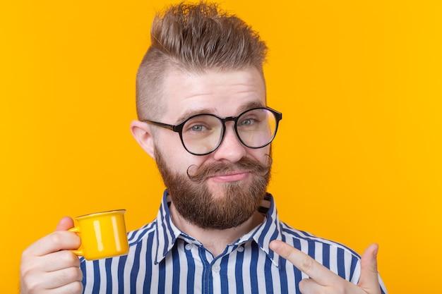 Ritratto di un bel giovane sicuro di sé con gli occhiali con la barba con una piccola tazza gialla su una parete gialla. buongiorno concetto.
