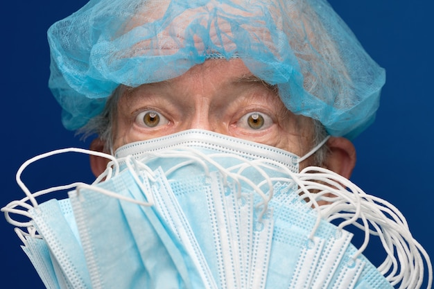Ritratto di uno sguardo pauroso adulto anziano in maschera medica che copre naso, bocca da sars, infezione 2019-ncov. il maschio ha inoltre il viso coperto con molte maschere respiratorie che impediscono il contatto con le persone