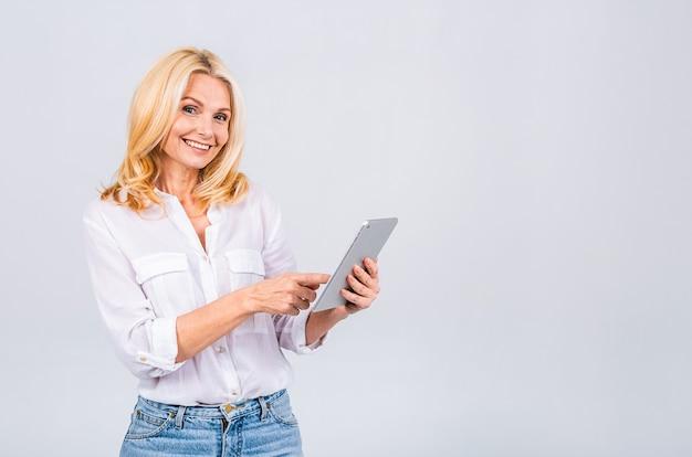 Ritratto di donna bionda matura invecchiata senior con computer tablet, isolato su sfondo bianco.
