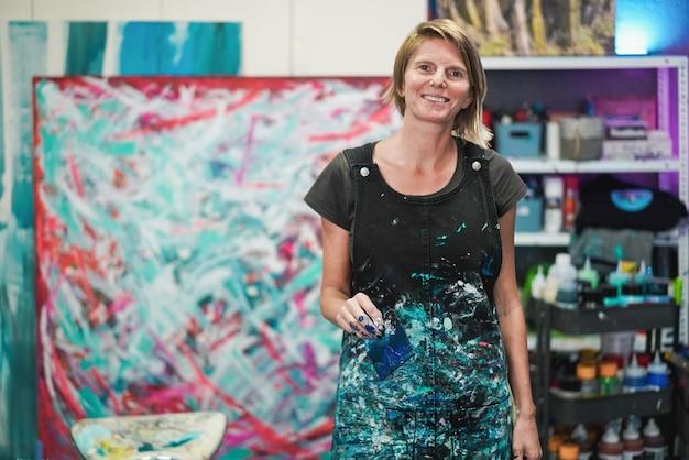 Ritratto di artista senior dipinto nel suo studio atelier a casa - focus sul viso