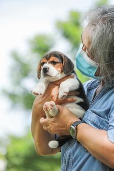 Ritratto di donna senior asia con maschera protettiva e con il suo cucciolo di cane che gioca al parco.