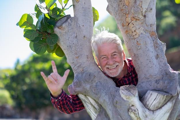 Ritratto di un uomo barbuto anziano che si gode all'aperto in un parco pubblico in piedi tra due tronchi d'albero. anziani allegri con i capelli bianchi e la camicia a scacchi