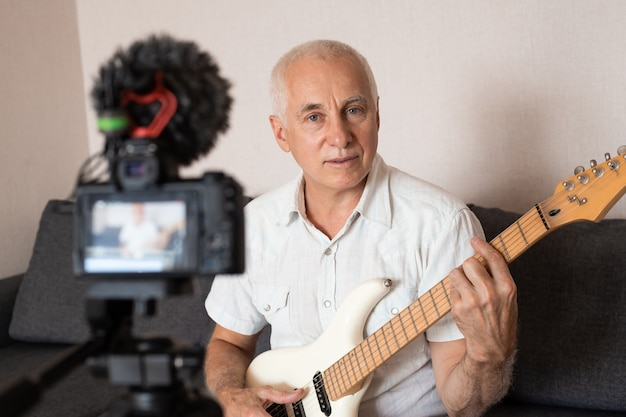 Ritratto di blogger senior a suonare la chitarra dal suo studio di registrazione a casa. imparare il concetto online.