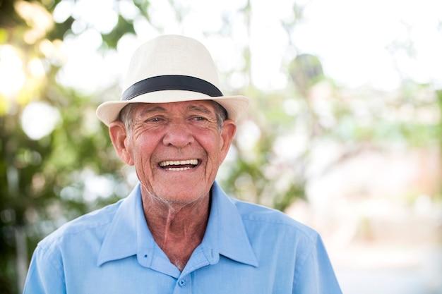 Ritratto di uomo brasiliano anziano con cappello bianco guardando un punto nel tramonto e sorridente. forma orizzontale, copia dello spazio.