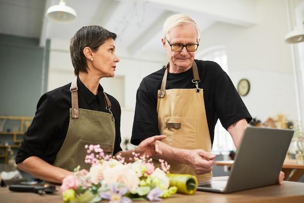 Ritratto di titolari di aziende senior che utilizzano insieme laptop durante la gestione dello spazio di copia del negozio di fiori