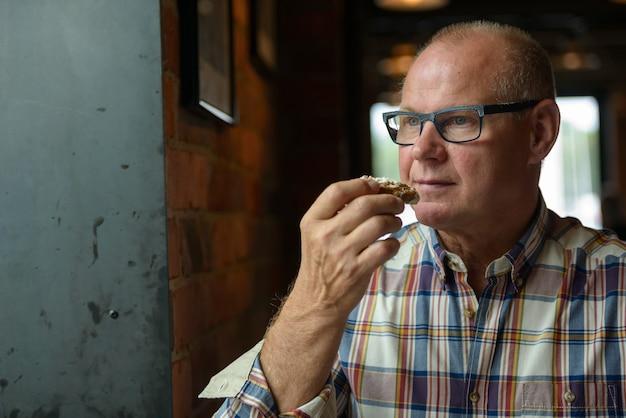 Ritratto dell'uomo d'affari maggiore che mangia biscotto al negozio di caffè
