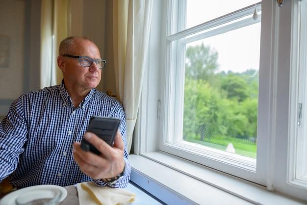 Ritratto di uomo d'affari senior utilizzando il telefono e guardando fuori dalla finestra a casa