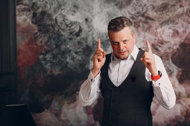Ritratto dell'uomo d'affari senior in maglia con le dita su. crescita del business e concetto di successo.