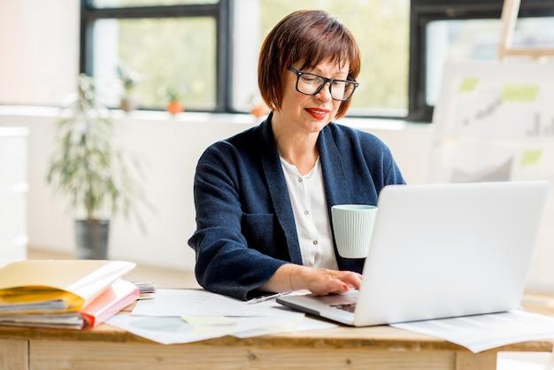 Ritratto di una donna d'affari anziana che lavora con documenti e laptop nel luminoso e moderno interno dell'ufficio