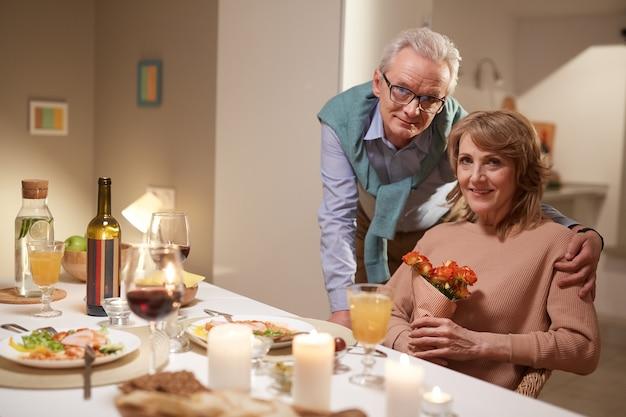 Ritratto di coppia senior con fiori sorridere alla telecamera durante la cena serale a casa