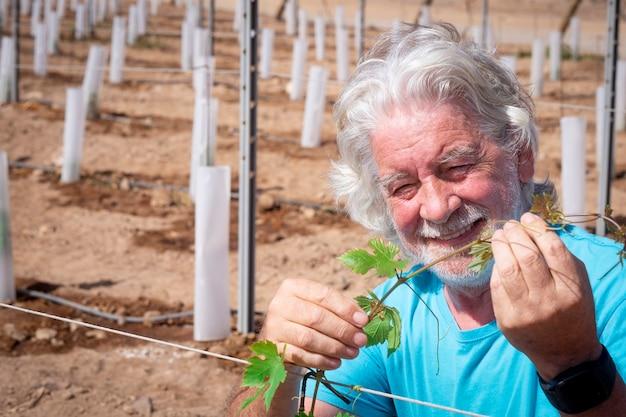 Ritratto di un anziano agricoltore controlla attentamente i germogli della sua nuova vigna sorridendo felicemente