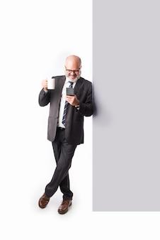 Ritratto di un anziano uomo d'affari asiatico indiano anziano appoggiato al muro e guardando la telecamera