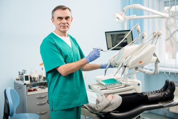 Ritratto del dentista maschio senior con gli strumenti dentali nell'ufficio dentale.