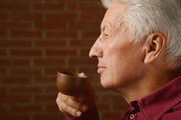 Ritratto di un uomo anziano che beve una tazza di caffè