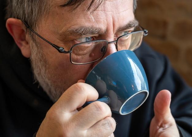 Ritratto di uomo anziano che gode della tazza di caffè nella caffetteria