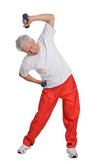 Ritratto di un uomo anziano che si esercita con i manubri su sfondo bianco