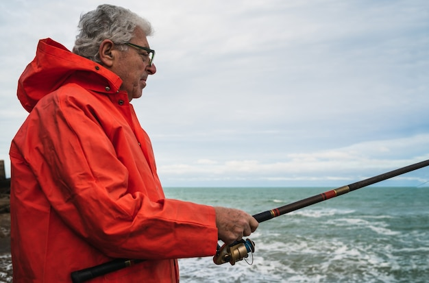 Ritratto di un uomo anziano che pesca in mare, godersi la vita.