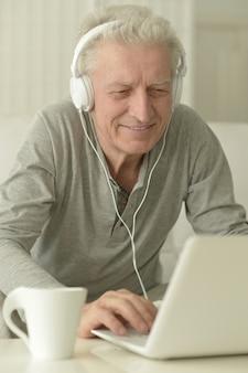 Ritratto di uomo anziano in cucina a casa con laptop