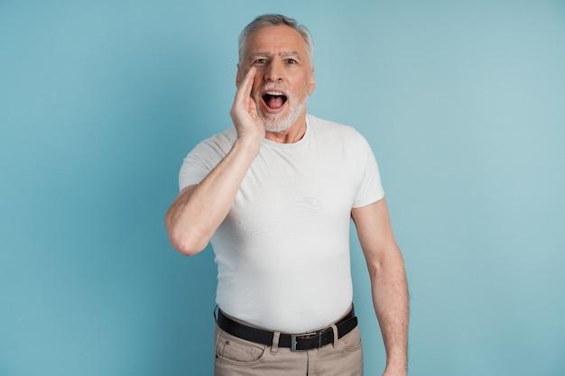Ritratto di un uomo anziano in cerca di qualcuno, si mette la mano alla bocca e chiama qualcuno