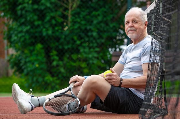 Ritratto di uomo anziano giocando a tennis in un esterno, sport in pensione, concetto di sport