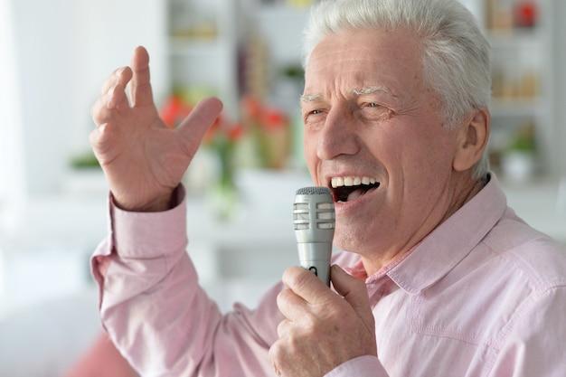 Ritratto di un uomo anziano che canta nel microfono