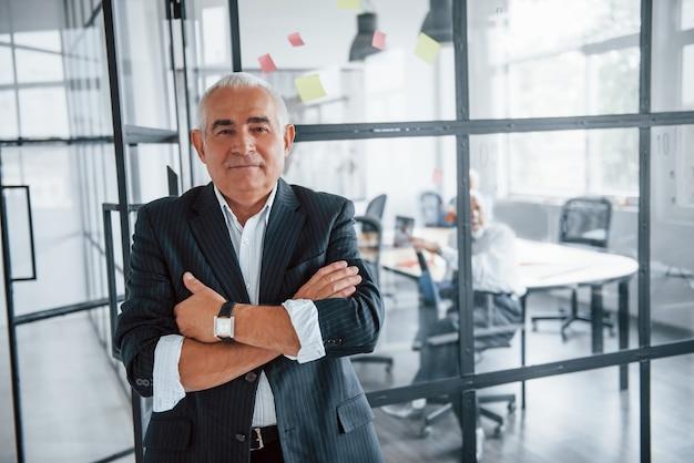 Ritratto di un uomo anziano che si trova di fronte a un gruppo di anziani di architetti d'affari anziani che hanno una riunione in ufficio.