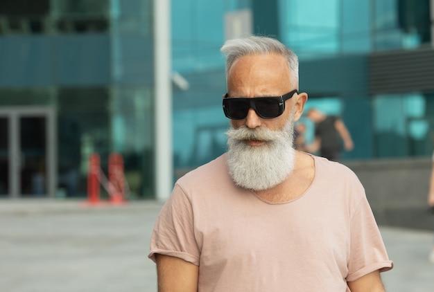 Ritratto di uomo anziano che indossa abiti casual che guarda lontano. uomo maturo con la barba che cammina per strada in una giornata estiva.