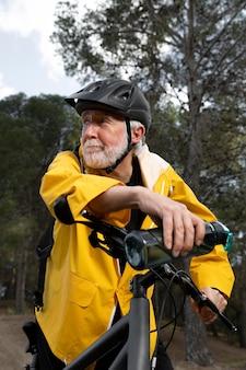 Uomo anziano del ritratto con la bici sulla montagna